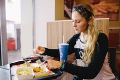 Женщина есть фаст-фуд в кафе Стоковые Фотографии RF