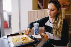 Женщина есть фаст-фуд в кафе Стоковые Фото