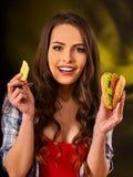 Женщина есть фраи и гамбургер француза на таблице стоковая фотография