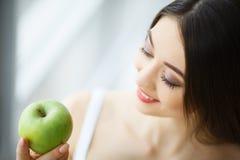 Женщина есть яблоко Красивая девушка с белыми зубами сдерживая Яблоко Стоковое Изображение