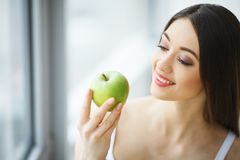 Женщина есть яблоко Красивая девушка с белыми зубами сдерживая Яблоко Стоковое Изображение RF