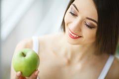 Женщина есть яблоко Красивая девушка с белыми зубами сдерживая Яблоко Стоковые Фото