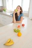 Женщина есть яблоко с плодоовощами на счетчике кухни Стоковое Изображение