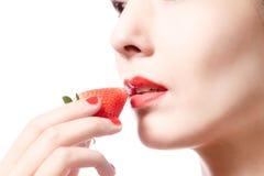 Женщина есть luscious зрелую красную клубнику Стоковая Фотография