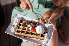 Женщина есть waffles Бельгии с соусом шоколада Стоковое Изображение RF