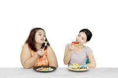 Женщина ест donuts и глумиться ее друг Стоковая Фотография RF