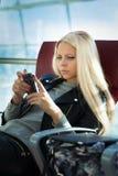 Женщина детенышей довольно белокурая с arport мобильного телефона сидя Стоковое фото RF