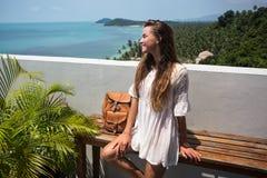 Женщина детенышей довольно стильная чувственная представляя на изумительном тропическом пляже с голубым океаном наслаждается ее п Стоковые Фото