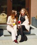 Женщина 2 детенышей довольно счастливая сидя outdoors и выпивая coffe Стоковая Фотография RF