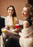 Женщина 2 детенышей довольно счастливая сидя outdoors и выпивая coffe Стоковое Фото