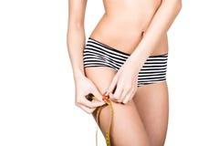 Женщина детенышей подходящая нося striped трусы, держа измеряя ленту с ее руками на бедренной кости, изолировала белую предпосылк Стоковые Изображения