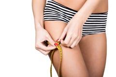 Женщина детенышей подходящая нося striped трусы, держа измеряя ленту с ее руками на бедренной кости, изолировала белую предпосылк Стоковые Фотографии RF