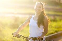 Женщина детенышей усмехаясь азиатск-кавказская на велосипеде стоковые изображения
