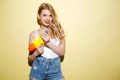 Женщина детенышей усмехаясь белокурая в лете одевает держать водяной пистолет Стоковые Изображения RF
