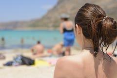 Женщина летних каникулов сидя на пляже наслаждается взглядом Красивая задняя сторона девушки внутри с кабелем на ее голове Стоковая Фотография