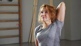 Женщина 35-40 лет приниманнсяая за йога в светлой йога-просторной квартире видеоматериал