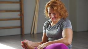 Женщина 35-40 лет приниманнсяая за йога в светлой йога-просторной квартире акции видеоматериалы