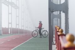 Женщина ехать велосипед на мосте в туманном утре, Киеве, Украине стоковые фото