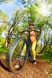 Женщина ехать горный велосипед на следе леса Стоковые Изображения RF