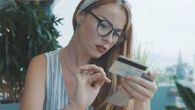 Женщина делает приобретение с кредитной карточкой на мобильном телефоне и имеет затруднения сток-видео