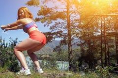 Женщина делает сидение на корточках Стоковое Изображение RF