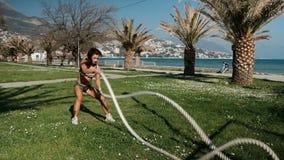 Женщина делает тренировку при 2 веревочки держа в оружиях, двигая fastly стоять на траве outdoors сток-видео
