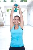 женщина делая двойное расширение с dumbbel подняла над ее головой Стоковая Фотография
