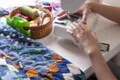 Женщина делая заплатку на швейной машине стоковое фото