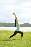 Женщина делая йогу в парке утра около моря Стоковая Фотография