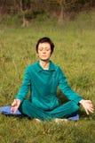 Женщина делая йогу в парке Стоковое Фото