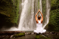 Женщина делая йогу около водопада Стоковые Изображения RF