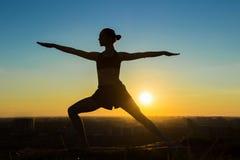 Женщина делая йогу Ashtanga в парке на заходе солнца Стоковое Изображение