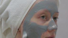 Женщина делая косметическую маску на ее стороне видеоматериал