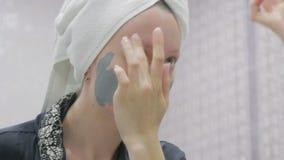 Женщина делая косметическую маску на ее стороне акции видеоматериалы