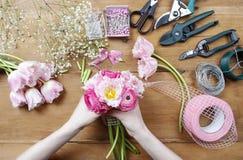 Женщина делая красивый букет розового персидского лютика Стоковая Фотография