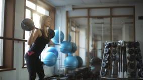 Женщина делая классику сидит на корточках при штанга стоя вверх, в спортклубе сток-видео