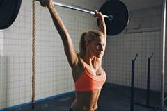 Женщина делая подниматься штанги crossfit Стоковое Фото