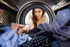 Женщина делая прачечную достигая внутреннюю стиральную машину стоковое изображение