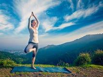 Женщина делая представление дерева Vrikshasana asana йоги в горы outdoors Стоковые Изображения RF