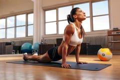 Женщина делая простирание ядра в спортзале стоковое фото rf