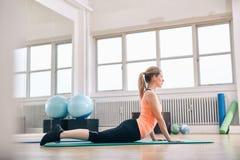 Женщина делая простирание ядра на циновке фитнеса стоковое фото