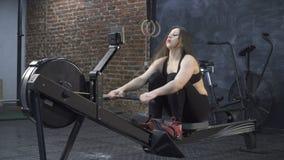 Женщина делая разминку машины rowing видеоматериал