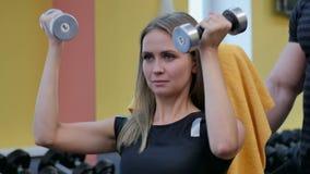 Женщина делая разминку с гантелями на спортзале видеоматериал