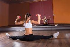 Женщина делая разделения и поднимая весы в студии стоковые изображения rf