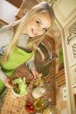 Женщина делая салат с овощами в кухне стоковые изображения