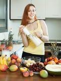Женщина делая свежий milkshake от плодоовощей стоковые изображения