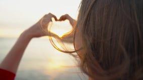 Женщина делая символ сердца с ее руками во время захода солнца на пляже сток-видео