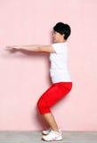 Женщина делая сидения на корточках над розовой стеной Стоковое фото RF