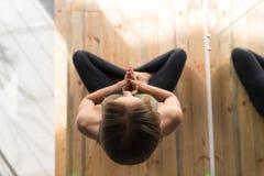 Женщина делая тренировки в спортзале, представление йоги лотоса девушки фитнеса спорта сидя Стоковое фото RF