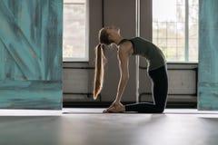 Женщина делая тренировки в спортзале, протягивать йоги тренировки девушки фитнеса спорта Стоковые Изображения